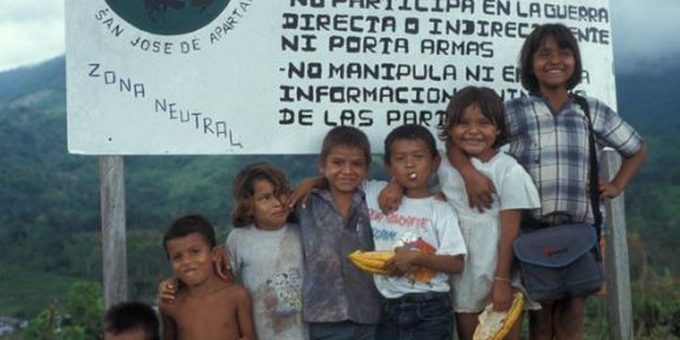 Kinder der Gemeinde San José de Apartado stehen vor einem Schild das auf die neutrale Zone hinweist.   © privat