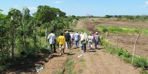 Bauern begehen ein Stück Land, das auf der einen Seite noch bewirtschaftet wird (links) und dessen andere Seite dem Landraub zum Opfer gefallen ist (rechts). El Tamarindo, Dep. Atlántico, Nordkolumbien. Dezember 2013. © Amnesty International