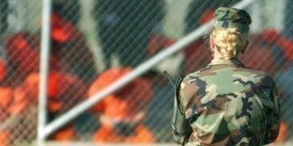 US-Soldatin bewacht Gefangene in Guantánamo, die kniend der Bruthitze ausgesetzt sind  © US DoD