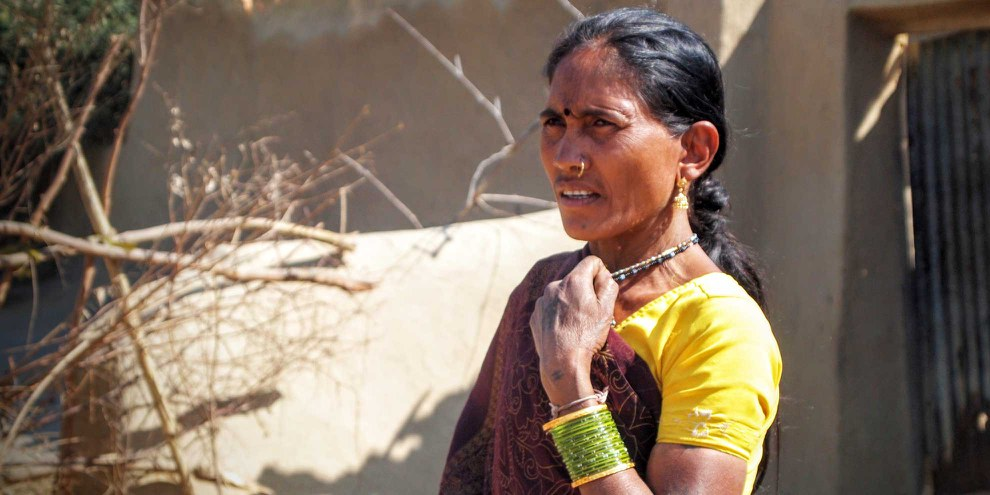 Die Adivasi-Frau Nirupabai neben ihrem Haus, das neun Tage zuvor zerstört worden war, um der Erweiterung der KusmundaMine Platz zu machen.All ihr Besitz und die Getreideernte eines Jahres wurden dabei vernichtet. Januar,2014.©AmnestyInternationalIndia