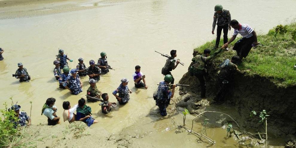 Sicherheitskräfte Myanmars begleiten hinduistische DorfbewohnerInnen zu Massengräbern, in welchen ihre Verwandten begraben wurden. Die Leichen von 45 Personen aus Ah Nauk Kha Maung Seik (in Maungdaw Township, Rakhine State) wurden Ende September 2017 in vier Massengräbern ausgegraben. Die Opfer gehören zu den  100 Menschen, die bei zwei Massakern der Arakan Rohingya Salvation Army (ARSA) am 25. August 2017 getötet wurden. © Privat