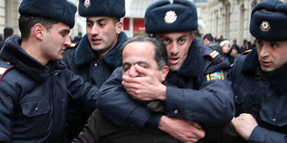 Polizisten bringen einen Aktivisten zum Verstummen. Baku, 12. März 2011. © AI