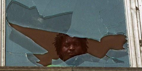 23. September 1991: Nach Angriffen auf eine Flüchtlingsunterkunft im sächsichen Hoyerswerda schaut ein Bewohner aus einem zerstörten Fenster: © Zentralbild / pa