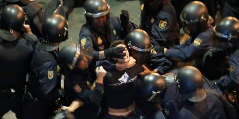 Polizisten nehmen einen Demonstranten in Madrid in die Mangel. © REUTERS / Sergio Perez