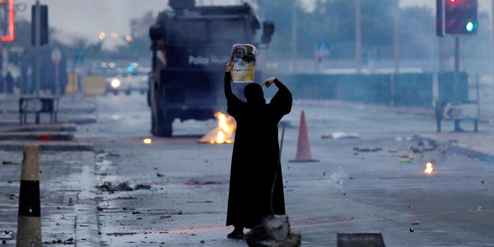 Eine Demonstrantin mit einem Bild eines schiitischen Geistlichen stellt sich vor bewaffnete Polizeiwagen.© REUTERS/Hamad I Mohammed