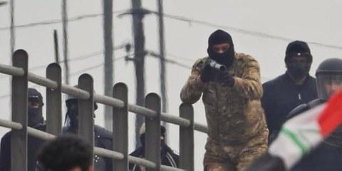 Irakische Sicherheitskräfte zielen auf Demonstranten auf einer Brücke über der Mohammed al-Qasim-Autobahn  in Bagdad, 21. Januar 2020.  @ Ali Dab Dab