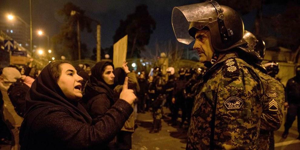 Eine Frau, die an einer Mahnwache zum Gedenken an die Opfer der Boeing 737 der Ukraine International Airlines teilnimmt, spricht nach der Versammlung vor der Amirkabir-Universität in der iranischen Hauptstadt Teheran am 11. Januar 2020 mit einem Polizisten.  ©ISNA/AFP via Getty Images