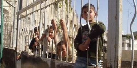 Palästinensische Kinder sitzen auf der Absperrung eines Checkpoints, der ihren Schulweg versperrt © CPT
