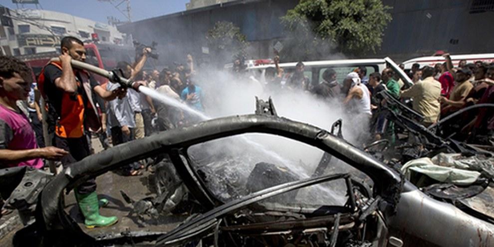 Feuerwehrmänner löschen nach einem Luftangriff in Gaza-Stadt ein brennendes Auto, 8. Juli 2014. © M. ABED/AFP/Getty Images