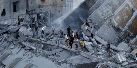 PalestinenserInnen inspizieren die Überreste eines Gebäudes in Gaza, welches durch einen Israelischen Luftangriff auf Gaza-Stadt am 26. August 2014 zerstört wurde. AFP / Getty Images