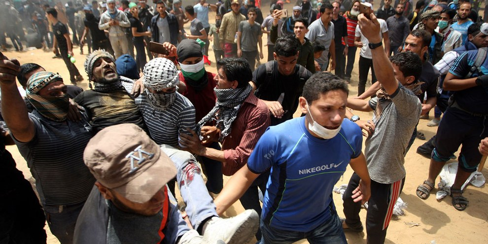 Palästinenser tragen im Gazastreifen einen verletzten Demonstranten weg. 14. Mai 2018. © Keystone/Newscom/Ismael Mohamad