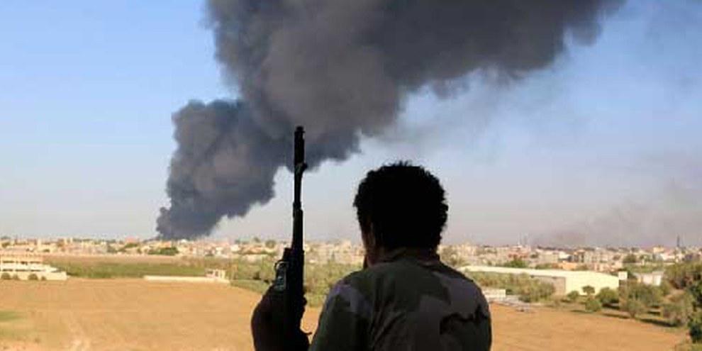 Ein Kämpfer der  Zintan-Brigaden beobachtet Raketeneinschläge in Tripolis. © REUTERS/Hani Amara