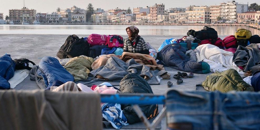 Eine Flüchtlingsfrau erwacht im Hafen von Chios, in welchem Flüchtlinge und MigrantInnen unter freiem Himmel übernachten. 5. April 2016. © Louisa Gouliamaki/AFP/Getty Images