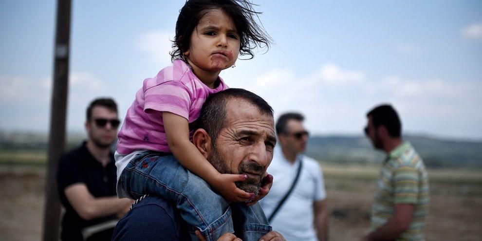 In Griechenland verlässt ein Syrer mit seiner Tochter das Idomeni Lager nach einer Räumung durch die griechische Polizei. © Shutterstock