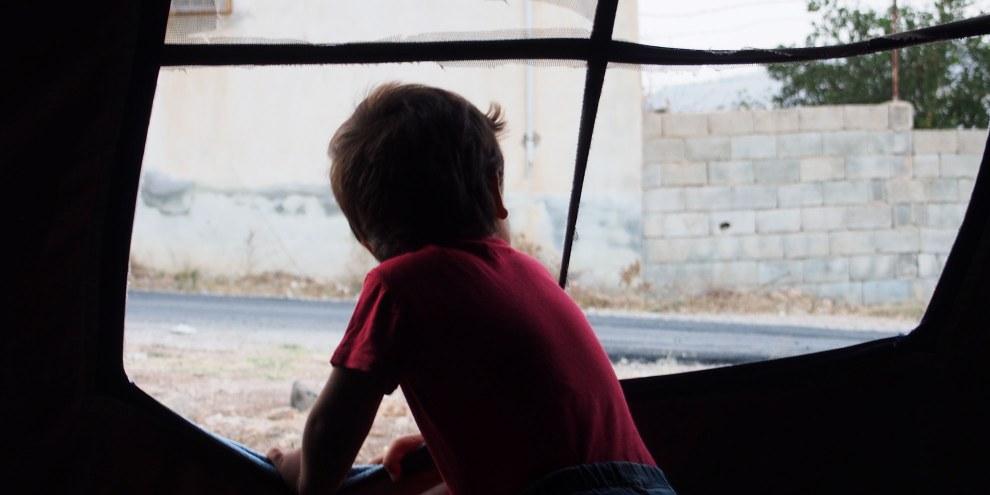 Ein Kind schaut aus einem Zelt bei Killis © Amnesty International