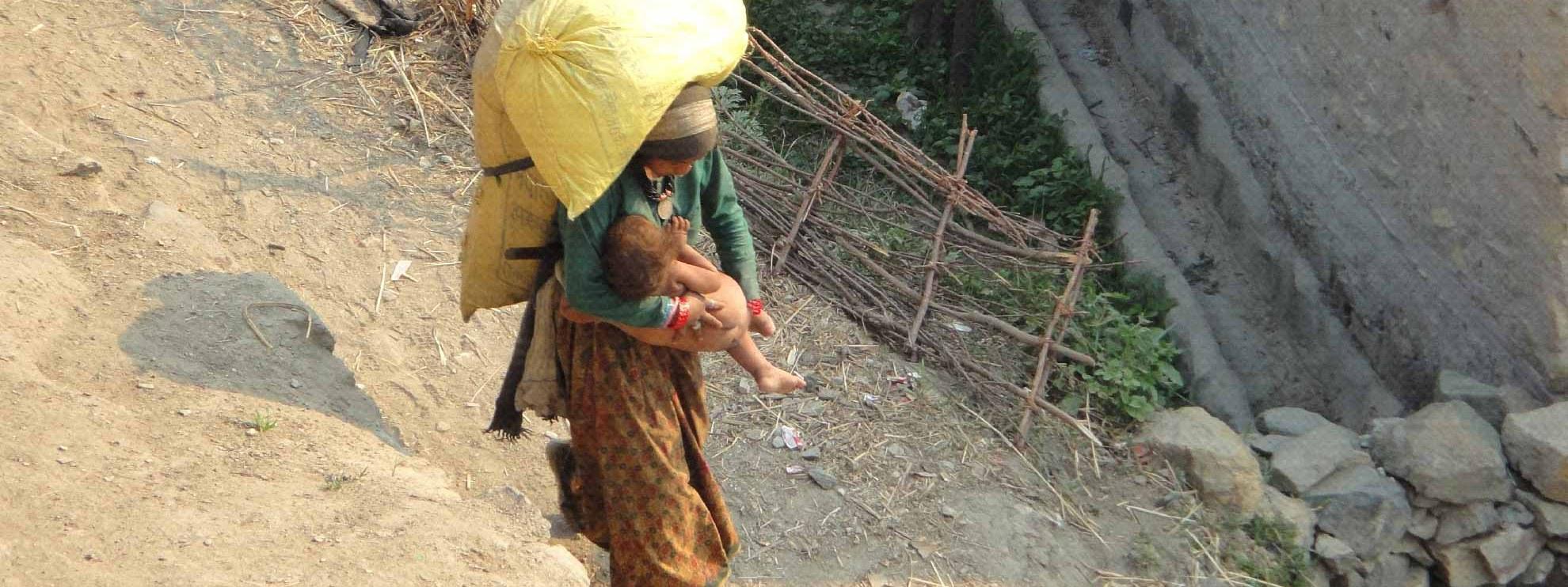Eine Frau trägt schwere Lasten und ein Kind im Mugu District, Nepal 2013 © Amnesty International