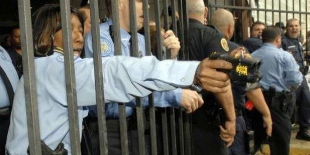 Eine Polizistin in New Orleans richtet eine Taser-Pistole auf Demonstranten © AP/PA Photo/Cheryl Gerber