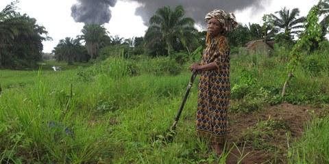 Die Bäuerin Taagaalo Christina Dimkpa Nkoo vor ihrem Land, das durch eine beschädigte Ölpipeline von Shell verschmutzt worden sei. Im Hintergrund Rauch aus der Pipeline in Kegbaara Dere, Rivers State, Nigeria. © Amnesty International
