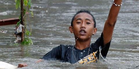 © Ein Junge auf der philippinischen Insel Luzon watet nach einem Sturm im Wasser. September 2017. © Reuters / Erik De Castro