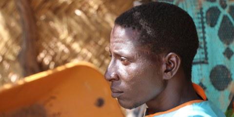 Abdallah, assis près de son abri dans le camp pour personnes déplacées où il vit avec ses enfants depuis que des attaques menées par un groupe armé les ont forcés à fuir leur village, situé à proximité de la frontière entre le Niger et le Mali, région de Tillabéri (Niger), 1er août 2021. « Les enfants ont entendu les coups de feu, ce souvenir les a hantés, a-t-il expliqué à Amnesty International. Ils n'arrivaient même plus à manger. Ils étaient complètement traumatisés [...] Quand vous êtes un père et que vos enfants ne vivent pas décemment, il n'y a pas de pire souffrance. » © Mamoudou L. Kane / Amnesty International