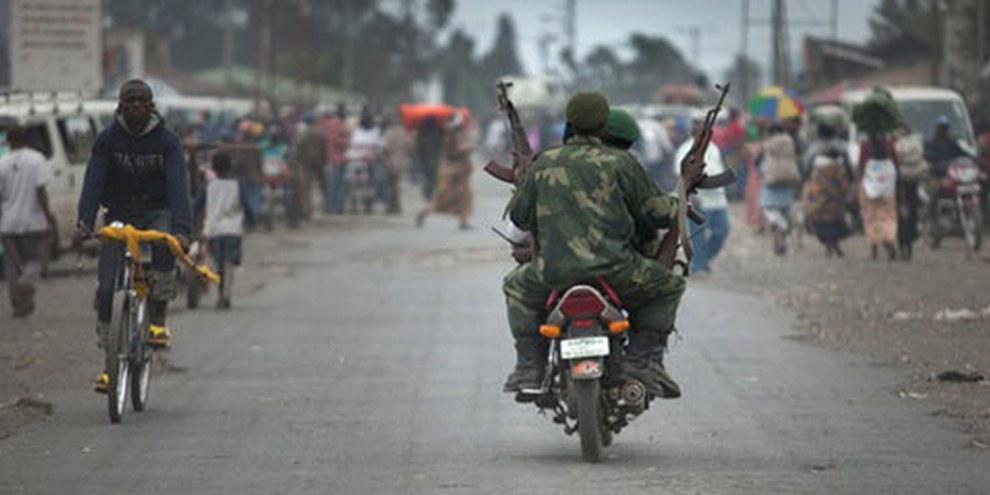 Un soldat des FARDC portant deux fusils AK-47 dans le village de Sake, Nord Kivu, tandis que la population fuit à cause des affrontements des FARDC avec les groupes rebelles, 30 avril 2012. © Blattman