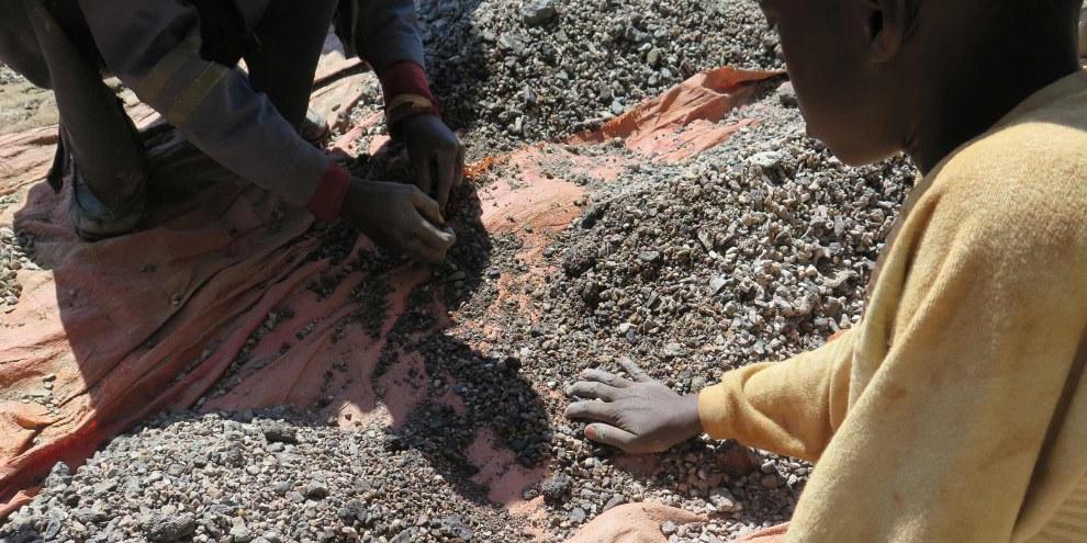 Charles, 13 ans, trie des pierres contenant du cobalt sur la rive du lac Malo Kapata en RDC. © Amnesty International.