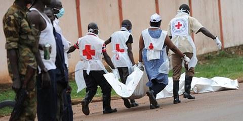 Des rebelles de l'ancienne Seleka observent des membres de la Croix-Rouge évacuant des corps après des affrontements le 6 décembre 2013, à Bangui. © SIA KAMBOU/AFP/Getty Images