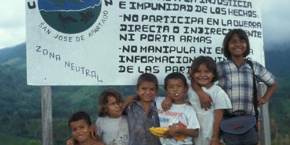 Des enfants de la communauté San José de Apartado posent devant un panneau qui annonce la zone neutre. © DR