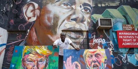 L'artiste kenyan Yegonizer et ses portraits de Donald Trump, devant une oeuvre murale de Bankslave représentant Obama. © Keystone/EPA/DAI KUROKAWA