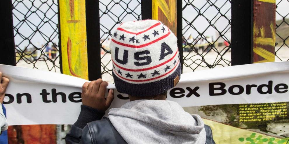 Un jeune garçon regarde Tijuana à travers le mur de la frontière séparant le Mexique des États-Unis © Amnesty International / Sergio Ortiz Borbolla