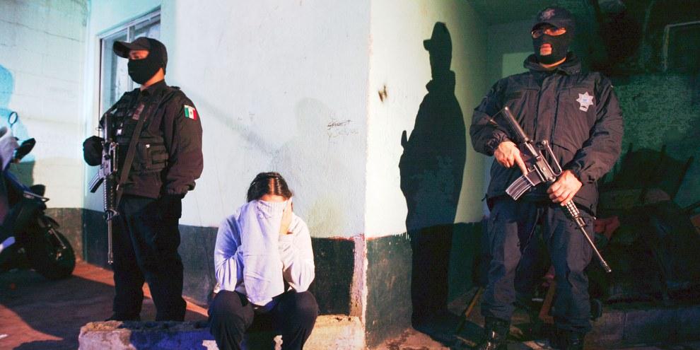 Des policiers arrêtant une femme à Mexico City, soupçonnée de trafic de drogue.  © Reuters