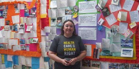 Ana María Pizarro de vant un mur composé de cartes de solidarité venues du monde entier  © SI Mujer