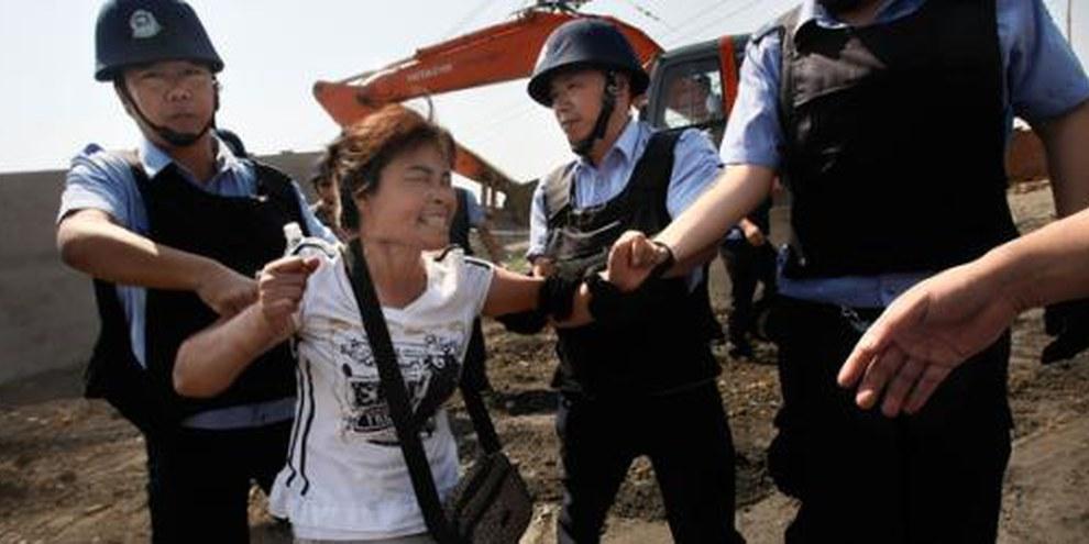 Des gens obligés de quitter leur foyer sont brutalisés par la police. © Fang Xinwu / Color China Photo / AP Photo