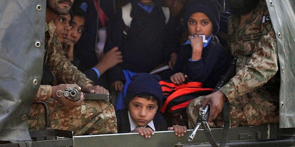 Des soldats pakistanais ont escorté les enfants rescapés de l'attaque d'une école dirigée par l'armée à Peshawar. © AFP/Getty Images