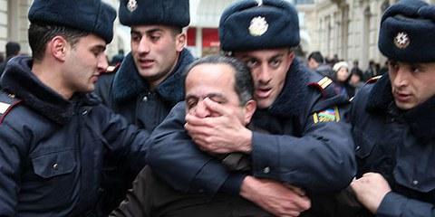 Activiste arrêté par des policiers pendant une manifestation, Bakou, 2011. © AI