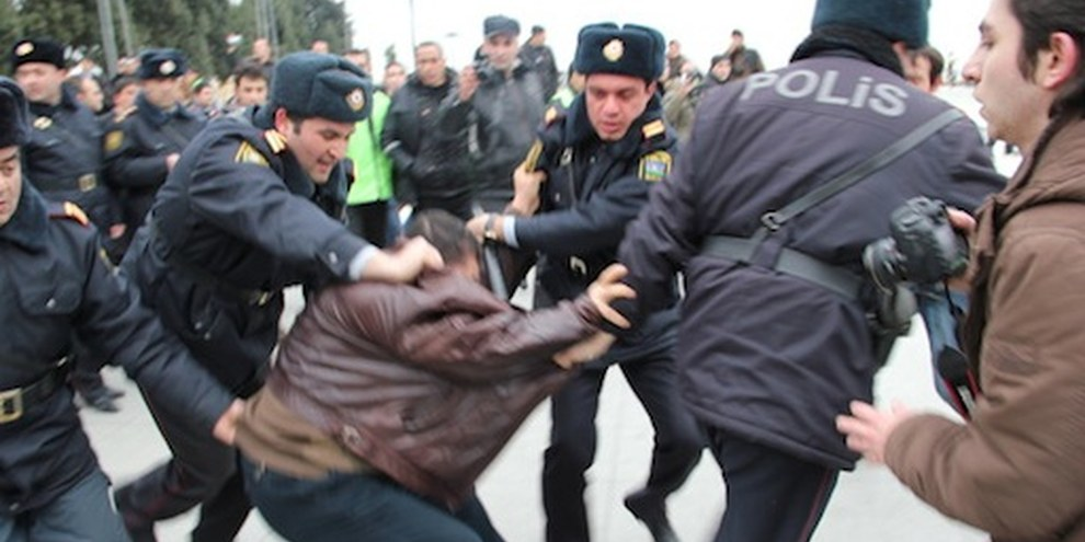 Quatre policiers traînent un activiste durant les protestations de mars 2011. © AI