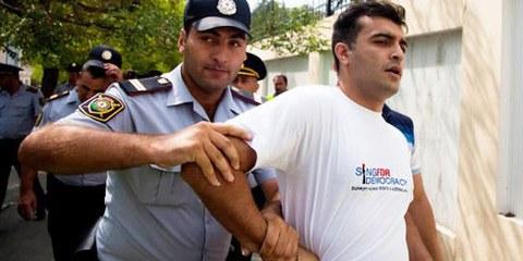 Des policiers arrêtent le défenseur des droits humains Rasul Jafarov. Il s'était engagé pour la démocratie dans son pays. Bakou, juin 2014. © RFE