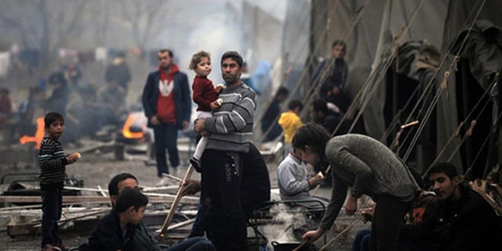 A Harmanli, le camp de requérants d'asile est, comme beaucoup d'autres, surpeuplé. Sur cette image, un Syrien tient un enfant dans ses bras. © NIKOLAY DOYCHINOV/AFP/Getty Images
