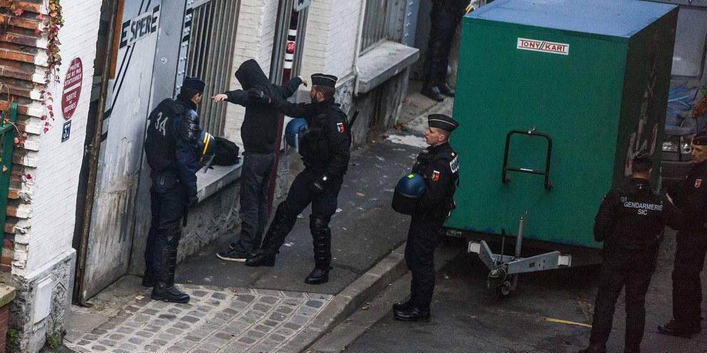 Un officier de police fouillant un homme durant un raid dans un immeuble situé au Pré-Saint-Gervais (nord de Paris), le 27 novembre 2015. © LAURENT EMMANUEL/AFP/Getty Images