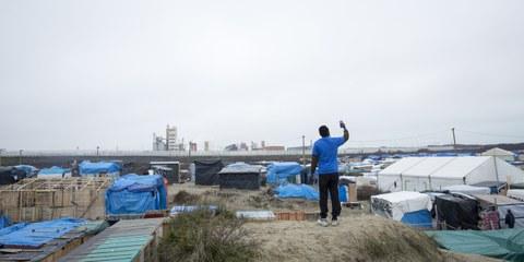 Un résident de la «Jungle» à Calais cherchant un signal réseau sur son téléphone.  © Richard Burton/Amnesty International
