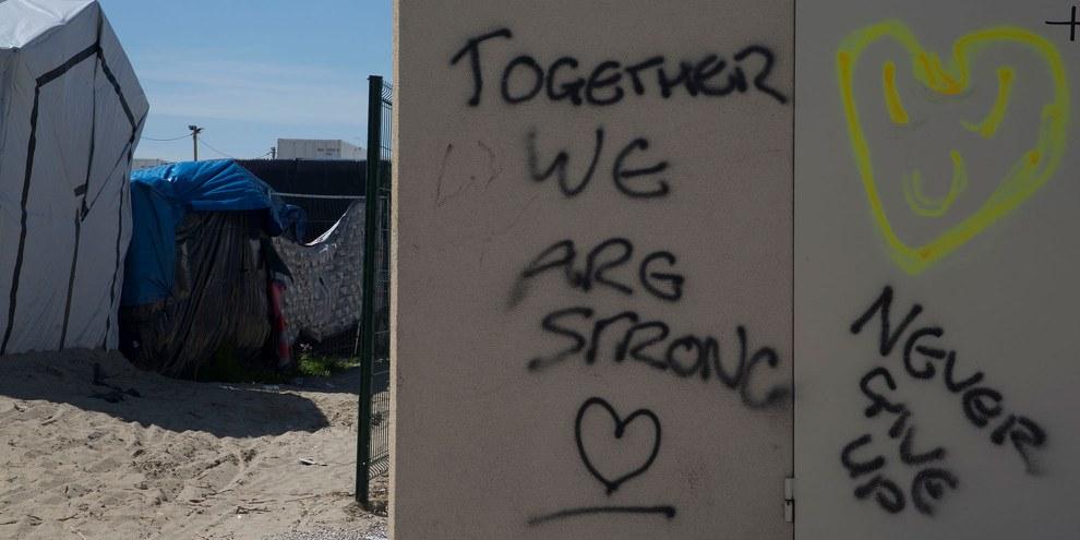Message de solidarité dans un camp de réfugiés à Calais, en France © Amnesty International
