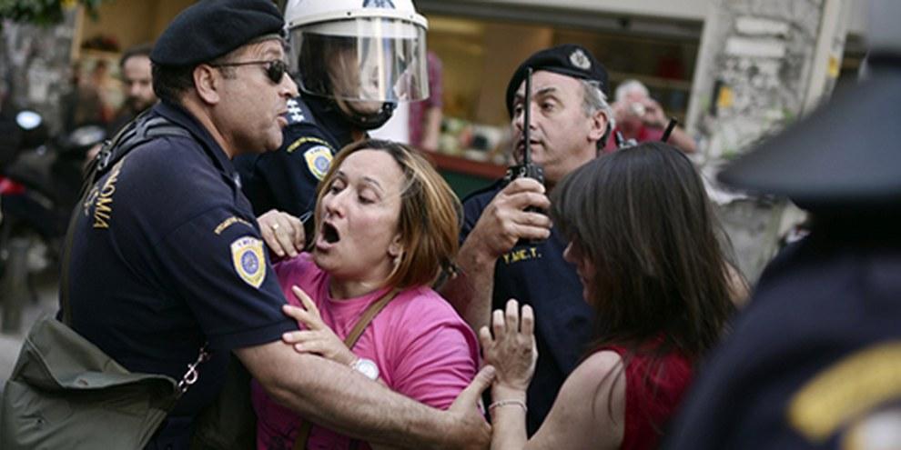 Des nettoyeuses en grève sont repoussées par la police antiémeutes devant le ministère des Finances à Athènes le 12 juin. © AFP / GettyImages