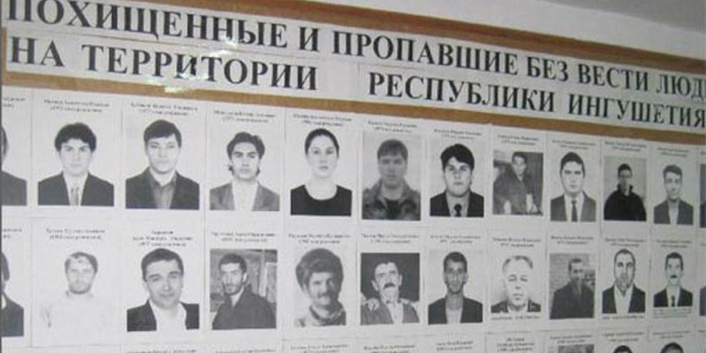MASHR, une organisation de défense des droits humains dans l'Ingouchie, a placardé des photos de personnes disparues depuis 2002. © AI