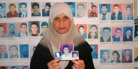 Une femme algérienne montre les photos de ses proches disparus © Amnesty International