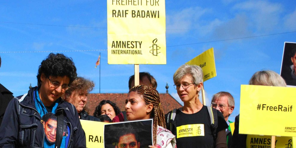 L'épouse de Raif Badawi, Ensaf Haidar (elle tient la photo), à Berne © Amnesty International