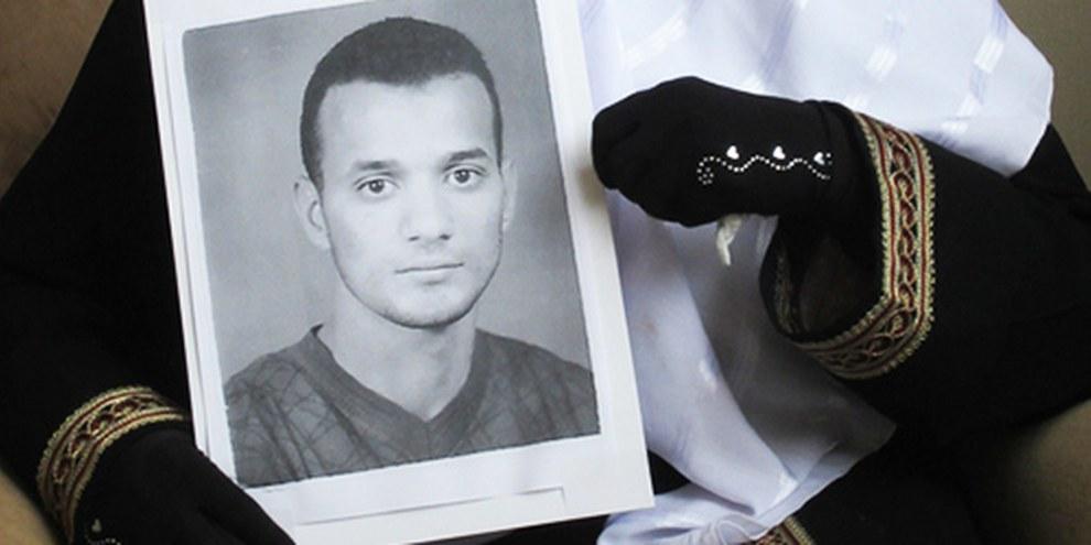 Une photographie d'Ahmad Amer Abd al-Qader, prisonnier exécuté, tenue entre les mains de sa mère. © AI