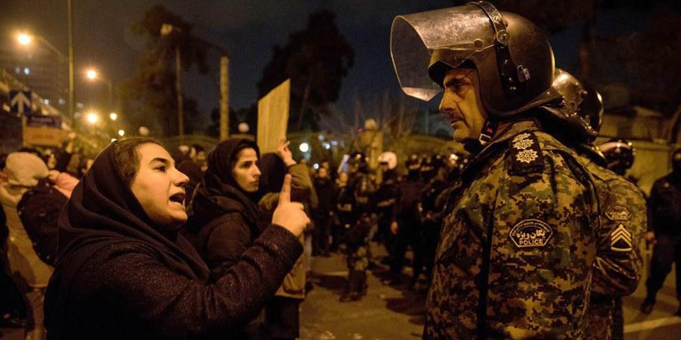Une femme participant à une veillée à la mémoire des victimes du Boeing 737 d'Ukraine International Airlines parle à un policier après le rassemblement devant l'Université Amirkabir dans la capitale iranienne, Téhéran, le 11 janvier 2020. ©ISNA/AFP via Getty Images