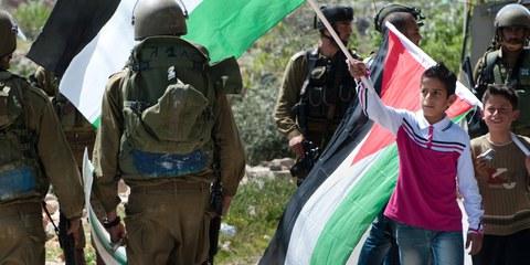 Un garçon palestinien brandit un drapeau en face d'un soldat israélien, lors d'une manifestation contre la barrière de séparation à Al-Masara. © Ryan Rodrick Beiler / Shutterstock.com