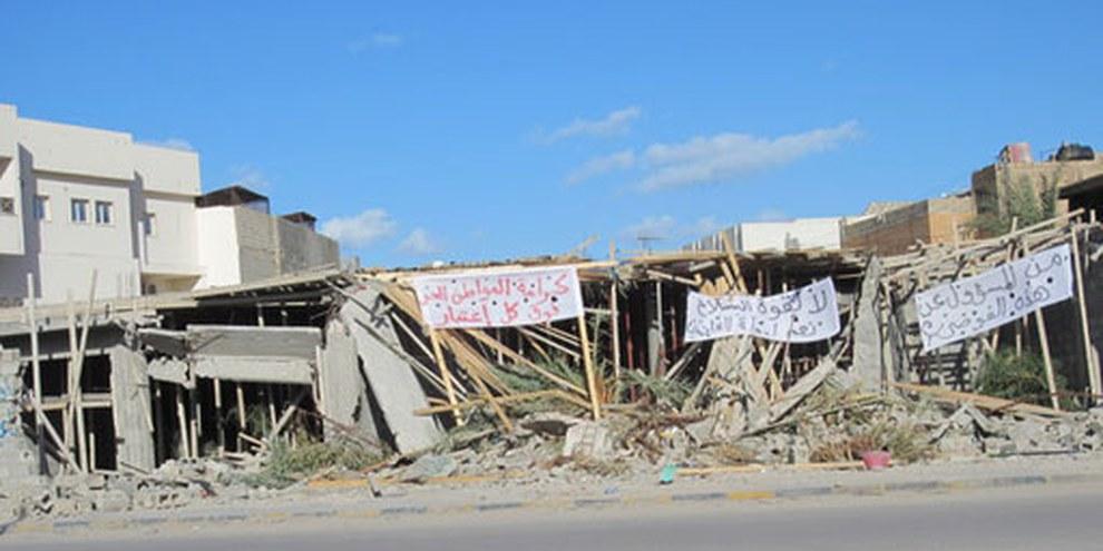 «La dignité des citoyens libres est prioritaire», «Non au pouvoir des armes et oui à un pays de lois», «Qui est responsable pour ce chaos?», peut-on lire sur des bannières posées  sur une maison démolie par les milices à Misrata en 2012. © AI