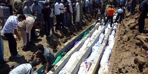 Des résident·e·s d'Houla enterrent des douzaines de victimes de l'attaque militaire sur la ville. © Sniperphoto.co.uk/Demotix